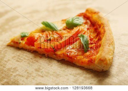Margherita pizza slice on cardboard background