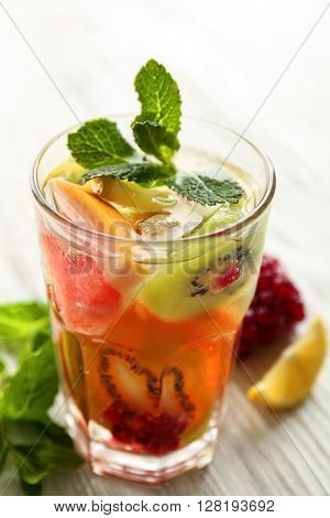 Refreshing cocktail with ice, mint, pomegranate seeds and slices of fruits on light wooden background