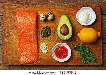Tasty ingredients of salmon tartare on cutting board, flat lay