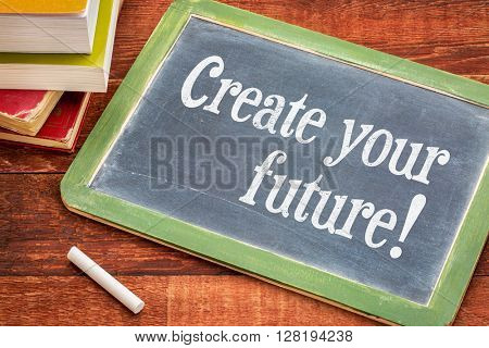 Create your future - inspirational phrase on a  slate blackboard with a white chalk and a stack of books against rustic wooden table