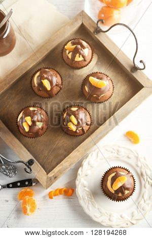 Tasty cupcakes with slice of mandarin and chocolate on a tray over light wooden background