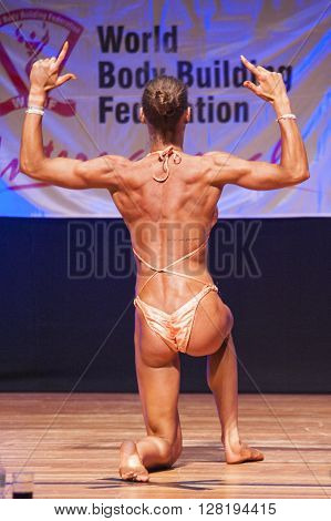 MAASTRICHT THE NETHERLANDS - OCTOBER 25 2015: Female fitness model flexes her muscles and shows her best physique in a back double biceps pose on stage at the World Grandprix Bodybuilding and Fitness of the WBBF-WFF on October 25 2015 at the MECC Theatre