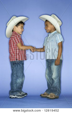 Hispanic and African American male child in cowboy hats shaking hands.