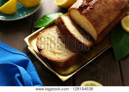 Delicious sweet cake bread in metal tray with lemons on wooden table closeup