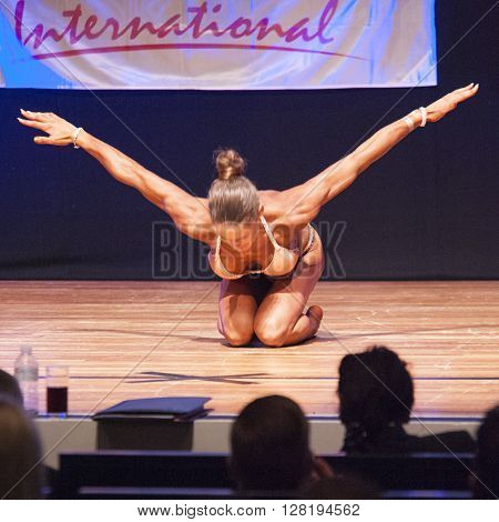 MAASTRICHT THE NETHERLANDS - OCTOBER 25 2015: Female fitness model flexes her muscles and shows her best physique in a front pose on stage at the World Grandprix Bodybuilding and Fitness of the WBBF-WFF