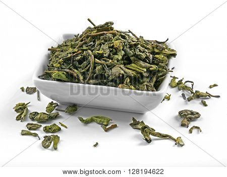 Dry tea leaves in bowl, isolated on white
