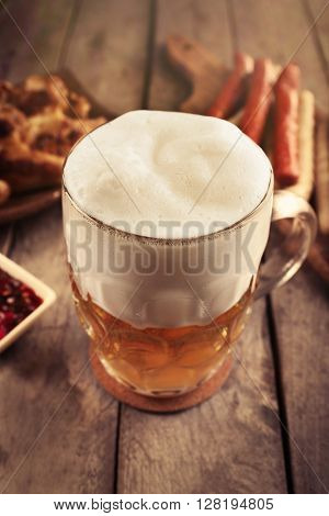 Glass of beer, chicken wings and grilled sausages on wooden table, close up