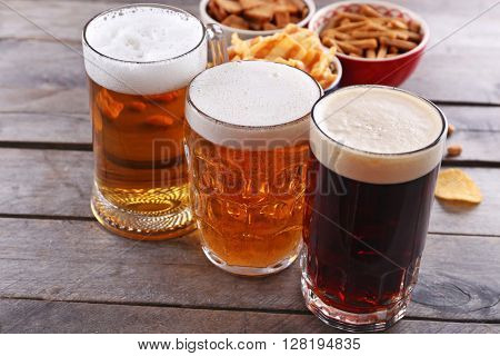 Various types of beer and snacks on wooden table