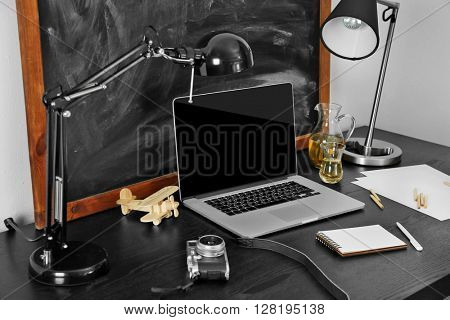 Desktop with notebook and other items on blackboard background