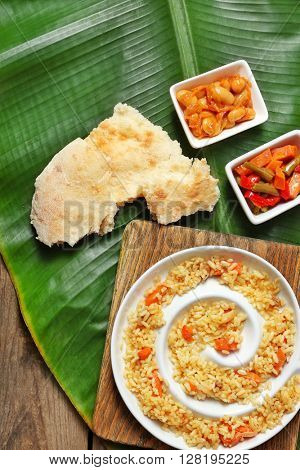 Fried rice with vegetables and flat bread on banana leaf over wooden background