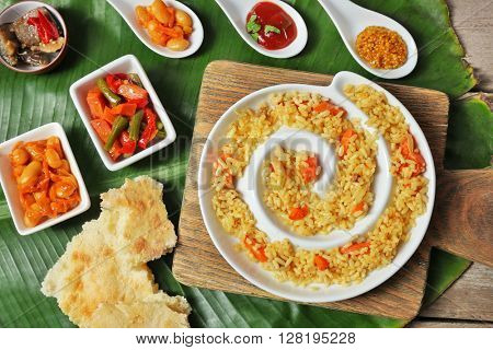 Fried rice with vegetables and flat bread on banana leaf background