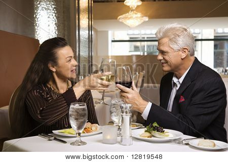 Caucasian mature adult male and prime adult female sitting at restaurant table toasting wine glasses.