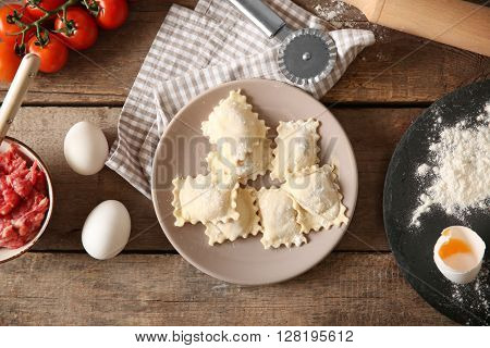Uncooked ravioli on plate on wooden table