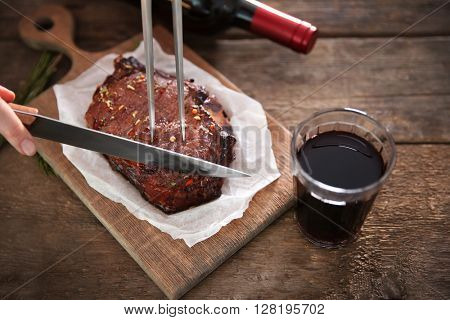 Roasted pork steak with wineglass, meat fork and knife on wooden background