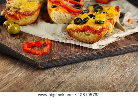 Hot pizza baguettes with olives, salami, ham and cheese on wooden table