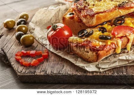 Hot pizza baguettes with olives, salami, cheese and tomatoes on wooden table