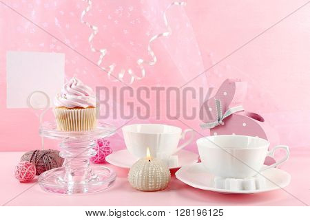 Tasty cupcake with tea set and decorations on pink background