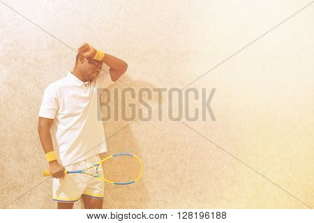 Squash player holding racket and touching his forehead after competition on squash court. Black man. Spotsman.