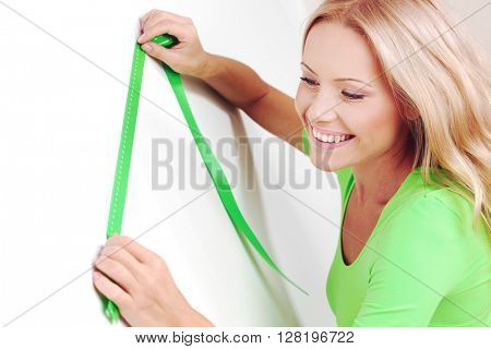 Happy ypung woman measuring wall with a measuring tape