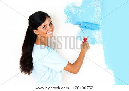 Young happy woman painting wall with paint roller