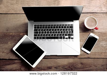 Modern laptop, smart phone and tablet with coffee cup on a wooden table
