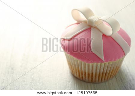Tasty cupcake with bow,  on light background