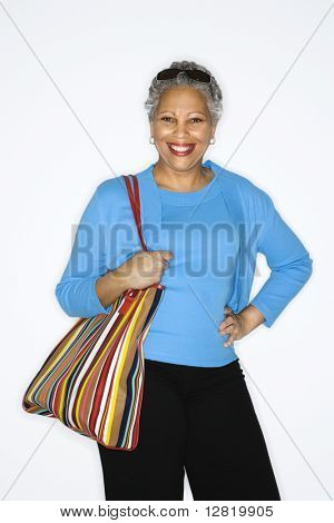 African American mature adult female holding big purse.