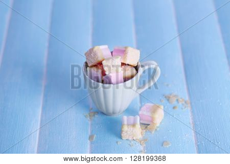 Tasty marshmallows with chocolate in cup on table, close up