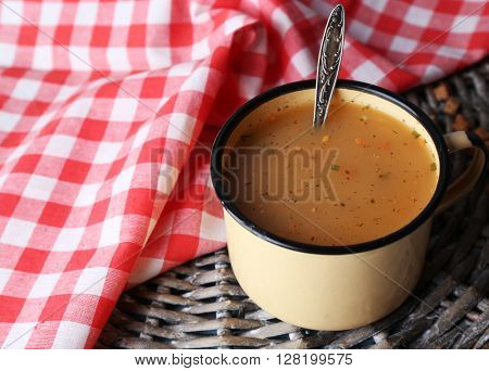 Mug of soup on wicker mat on a table closeup