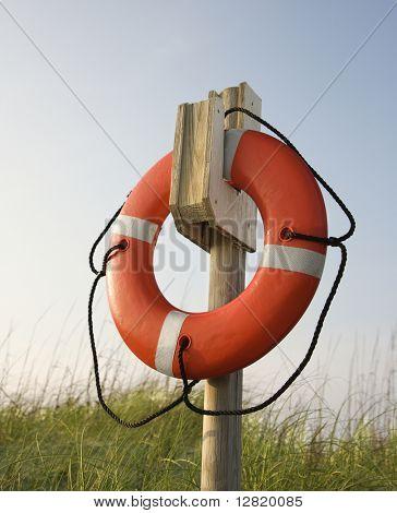 Life preserver hanging on post on beach on Bald Head Island, North Carolina.