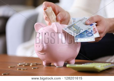 Young man with piggy bank on wooden table.
