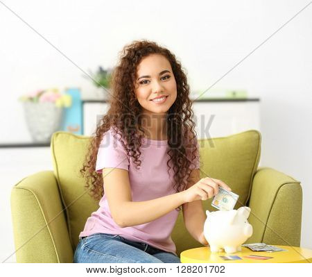 Beautiful young girl with piggy bank  and cash on armchair