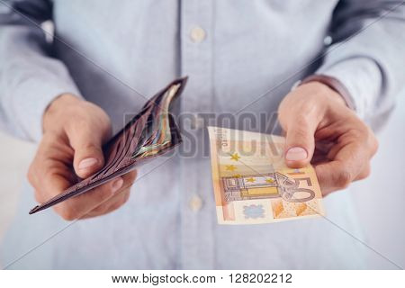 Male hands holding leather wallet with euros closeup