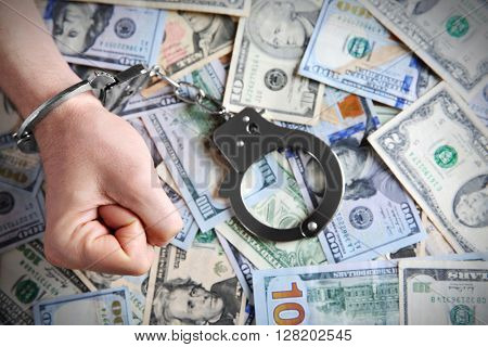 Man in handcuffs clenching fist on dollar banknotes background