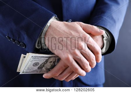 Man in handcuffs holding dollar banknotes, close up