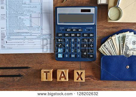Individual income tax return, calculator and notebook on wooden background