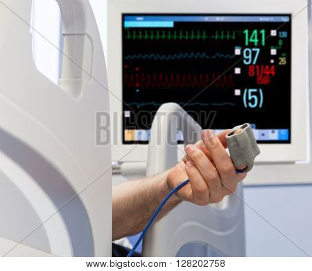Patient's Hand in Bed with Oximeter and Monitor on Background