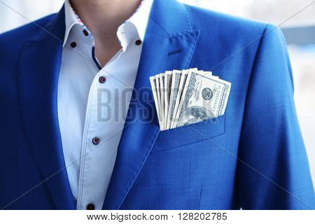 Man in a suit with dollar banknotes in pocket