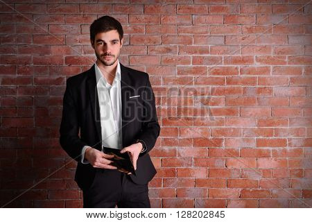 Attractive man in a suit showing a purse with banknotes on brick wall background