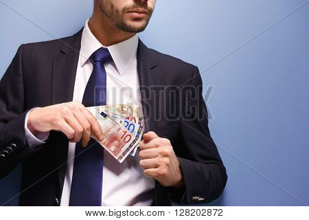 Attractive man hiding euro banknotes in suit on blue background