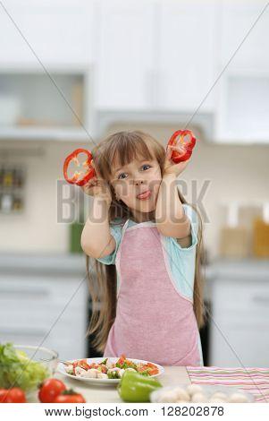 Little girl holding slices of red pepper.