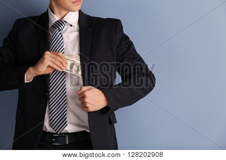 Man hiding dollar banknotes in suit on blue  background