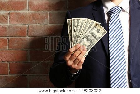 Man in a suit holding fan of dollar banknotes on brick wall background