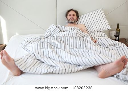 Drunk mature man sleeping in his bed