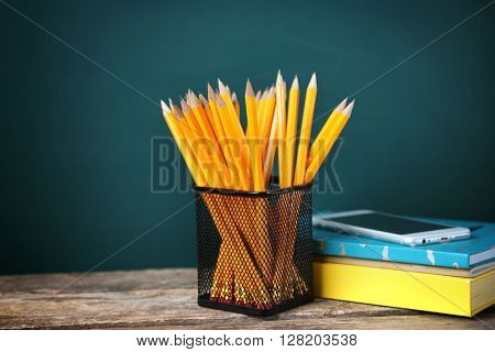 Many pencils in the metal holder on wooden table on green board background