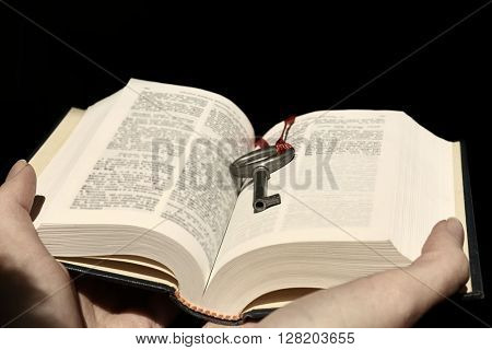 Hands holding a book with vintage key on black background.
