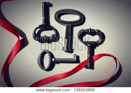 Vintage keys with a red ribbon on light paper background