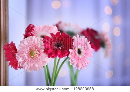 Bouquet of gerbers on blurred garland light background, closeup