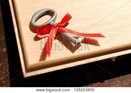 Vintage key in a wooden box with red ribbon.