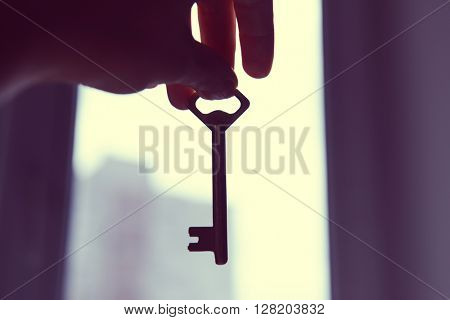 Female hand holding old key on blurred background